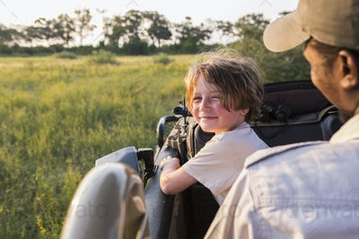 smiling 6 year old boy steering safari vehicle, Botswana
