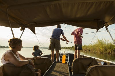 A group of tourists, family fishing from a boat on the Zambezi River, Botswana