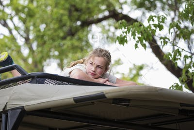 A teenage girl lying on the canopy of a safari vehicle under a tree.