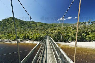 53846,Suspension bridge over tropical beach