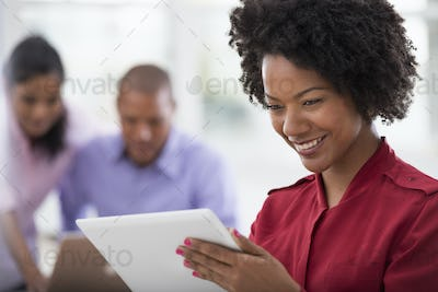 A business environment, two people in the background, and a young woman using a digital tablet.