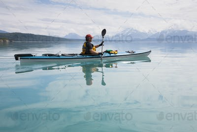 Man sea kayaking calm waters of an inlet in a national park.