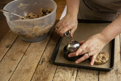High angle close up of person standing at wooden table, baking chocolate chip cookies.