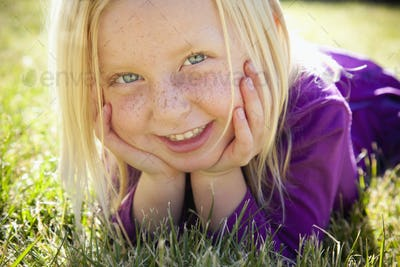 A young girl lying on the grass on her front with her chin resting on her hands. Laughing. Close up.