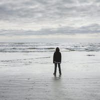 Teenage boy standing on vast beach, waves and overcast sky in distance