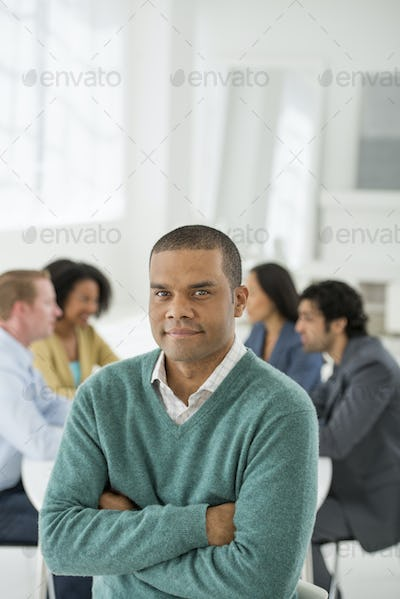 An office in the city. A group sitting down around a table. A man smiling confidently.