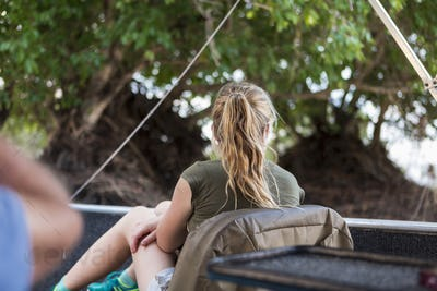Rear view of a twelve year old girl in a boat on a river in Botswana.