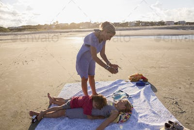 mother taking smart phone picture of her children on beach at sunset, Georgia