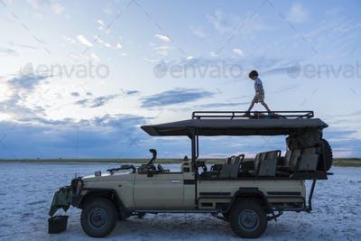 6 year old boy and older sister standing on top of safari vehicle, Nxai Pan, Botswana