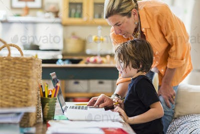 Adult woman helping her six year old son with a remote learning session on a laptop.
