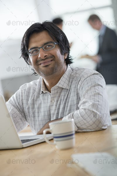 A young man in an office using a laptop computer.
