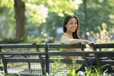 A woman sitting in a city park on a bench in the sunshine.