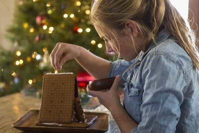 11 year old girl building a ginger bread house at home