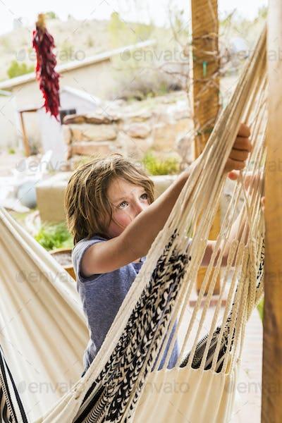 Six year old boy swinging in a hammock on a terrace.