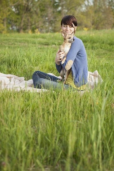 A young woman sitting in an open space, a grass field, on a blanket, holding a small chihuahua dog.