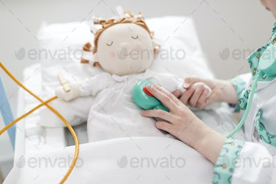 Young girl dressed as doctor using toy stethoscope on doll in make-believe hospital bed