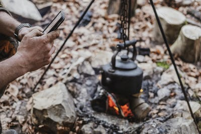 High angle close up of kettle over camp fire in a forest.