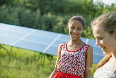 Two young girls on the farm, outdoors. A large solar panel in the field behind them.