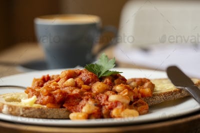 Close up of home made baked beans on sourdough bread in a cafe.