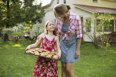 A young girl holding a tray of fresh baked cookies, and an adult woman leaning down to praise her.