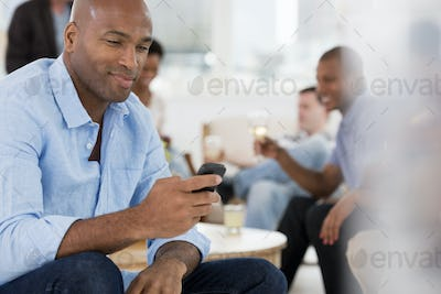 A group of people gathering together for a party or an office event. A man using his smart phone.