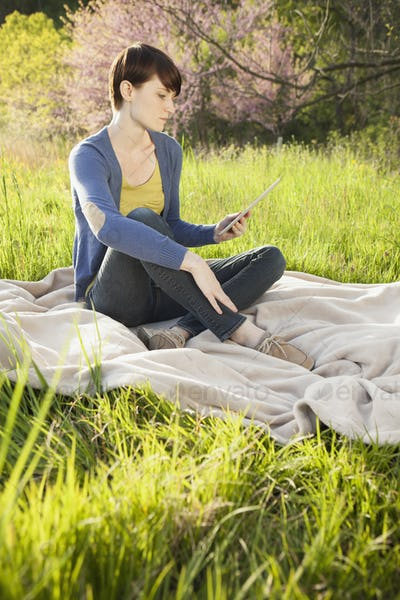 A young woman sitting in a field on a blanket, looking at a digital tablet.