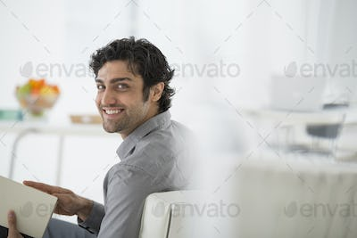 An office in the city. A man sitting holding a book, turning around and smiling.