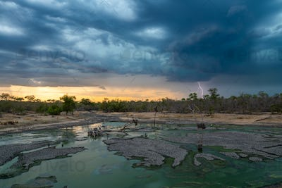 A landscape with a waterhoWaterhole and a sunset with dark clouds, rain and lightning
