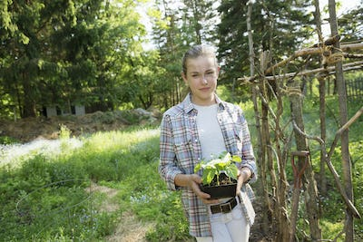 A girl in a checked shirt holding a plant
