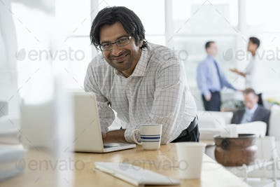 an office workplace. A young man using a laptop computer on a desk.
