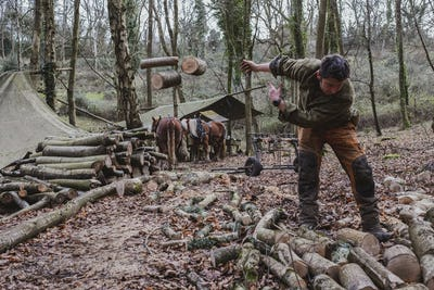 Logger working in a camp in a forest, throwing logs of wood onto heap.