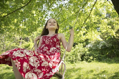 Summer. A girl in a sundress on a swing suspending from the branches of a tree.