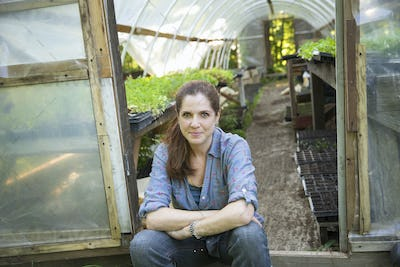 A woman sitting resting at the door of a glasshouse with benches full of young seedling plants.