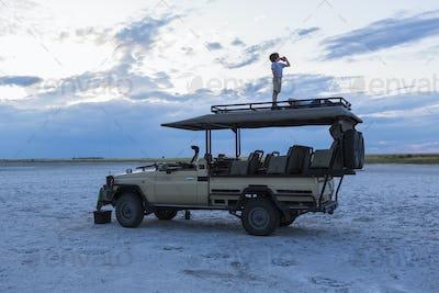 6 year old boy and older sister standing on top of safari vehicle, Nxai Pan, Botswana