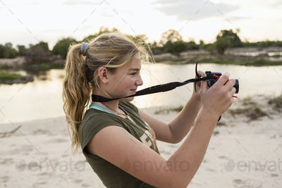 A twelve year old girl taking pictures on vacation in Botswana at sunset