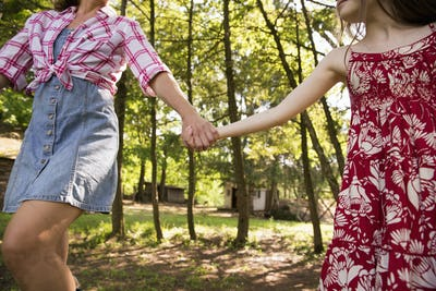 A woman and a young girl holding hands and running along under the trees.