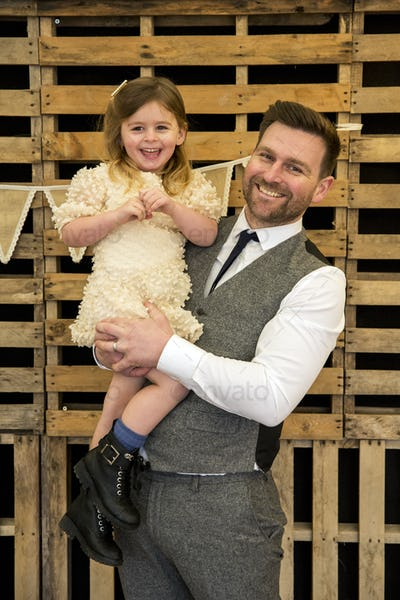 Portrait of bearded man hugging his young daughter during naming ceremony in an historic barn.