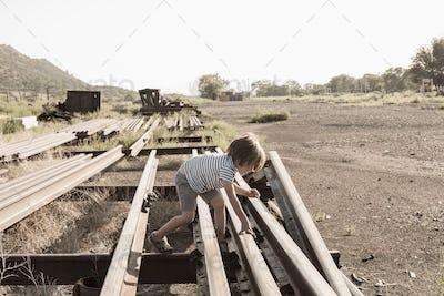 4 year old boy playing on railroad tracks, Lamy, NM.