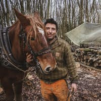 Portrait of a logger, standing in a forest camp with one of his work horses.