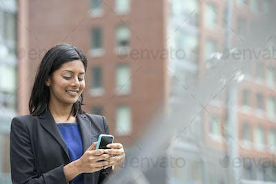 Business people out and about in the city. A young woman in a blue dress and grey jacket.