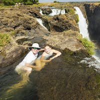 Mature man and girl, father and young teenage daughter in the water at Victoria Falls