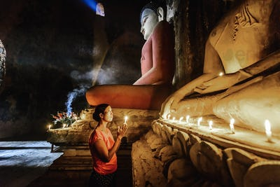 55051,Asian woman lighting candle in temple
