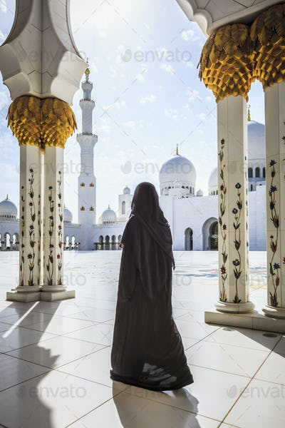 54959,Woman walking at Sheikh Zayed Grand Mosque, Abu Dhabi, United Arab Emirates