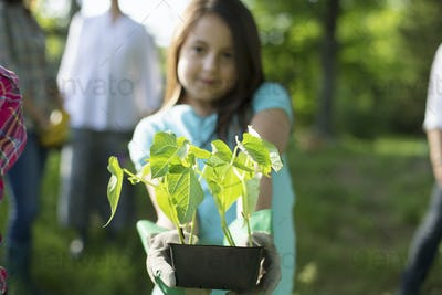 Summer party. A young girl holding out a tray of seedling plants.