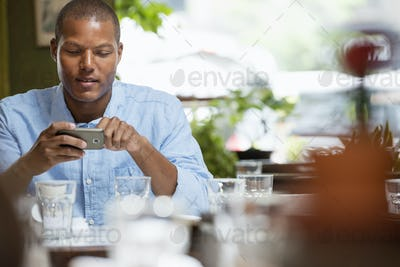 A man in a cafe by a table laden with glasses and crockery.  Checking his phone.