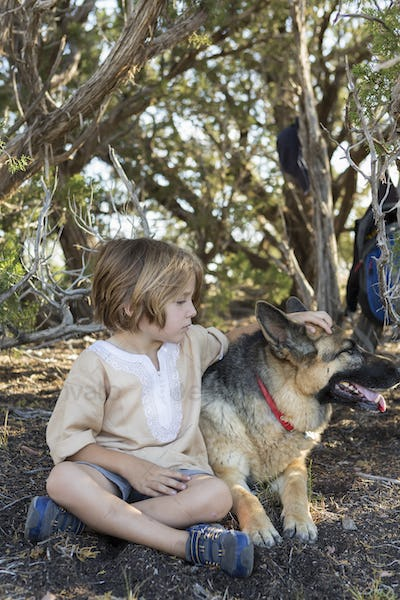 4 year old boy hiking with his German Shepherd