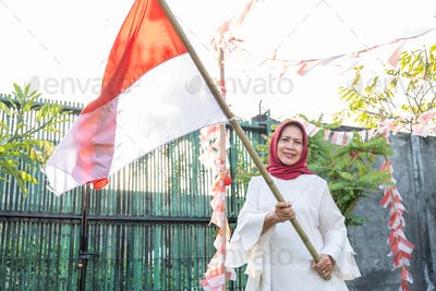 hijab grandmother holding an Indonesian-flagged bamboo stick