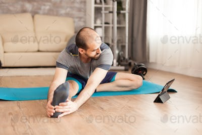 Fit man at home watching online stretching lesson