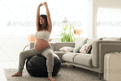 Pregnant woman doing relax exercises with a fitball