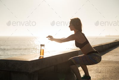 Fit woman doing exercices on summer sunset